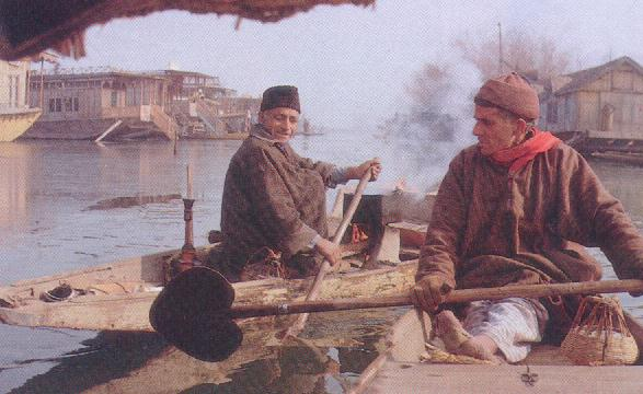The boat people of Kashmir oar across Dal Lake on a winter morning.